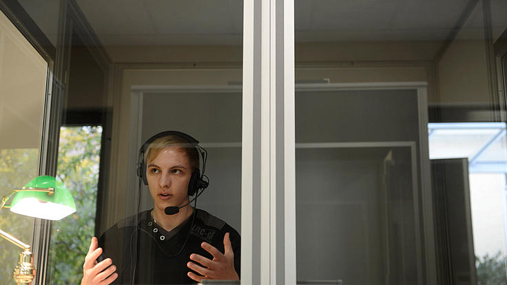 Ein Dolmetscher sitzt in einer Dolmetscherkabine.