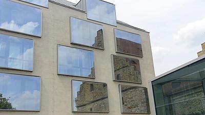 Ein altes Gebäude spiegelte sich in den Fenstern eines modernen Gebäudes.