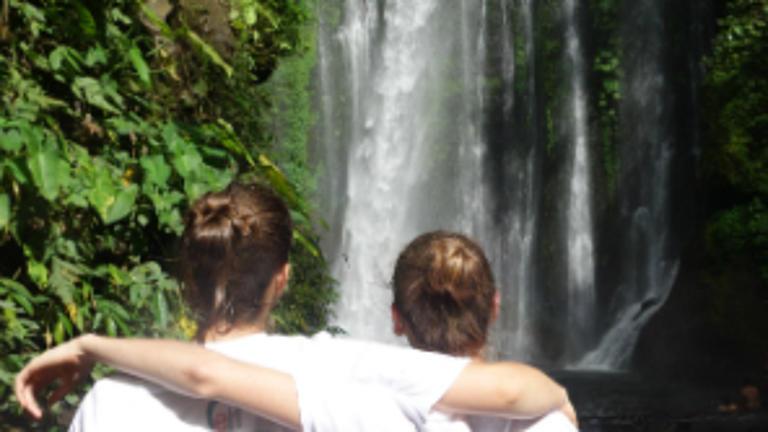 Studenten vor einem Wasserfall in Indonesien