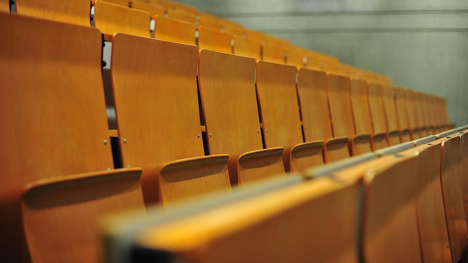 Leere Sitzreihen eines Vorlesungssaales.