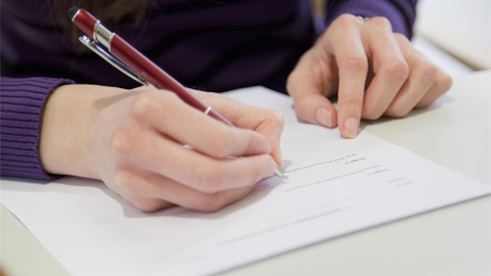 Jemand sitzt an einem Tisch mit einem Stift in der Hand und schreibt etwas auf ein Blatt Papier