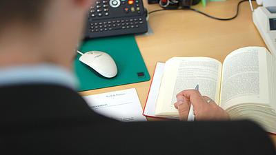 Ein Anwalt blättert in einem Gesetzbuch.