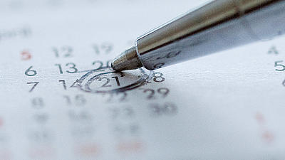 A silver pen marks on a calendersheet the 21th day.