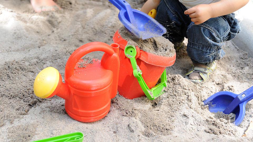 Ein kleines Kind spielt im Sandkasten.