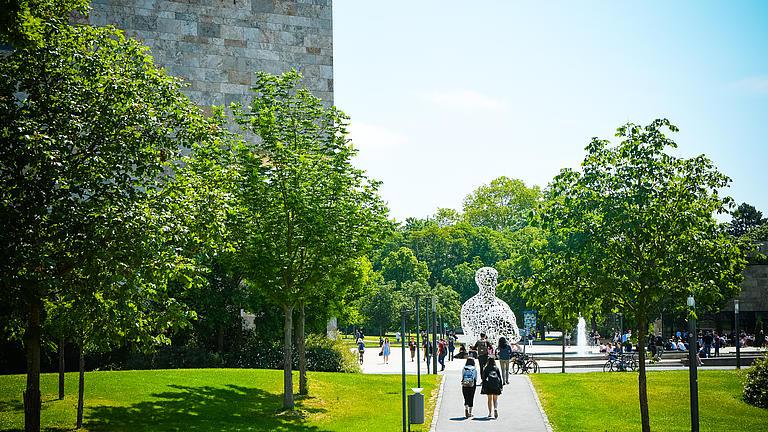 Ansicht der Universität mit grünen Bäumen, einen Weg mit Menschen, die darauf gehen