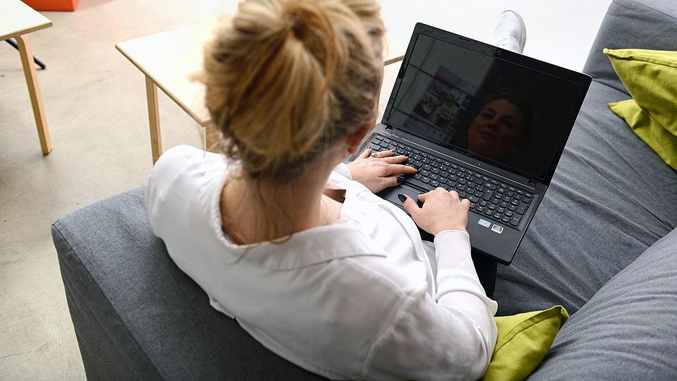 Eine Frau sitzt auf dem Sofa am Laptop.