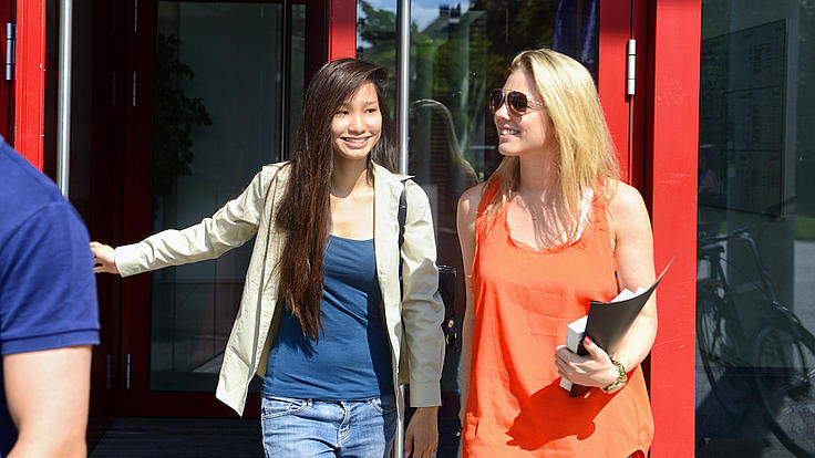 Zwei lächelnde junge Frauen kommen aus der roten Glastür eines Gebäudes.