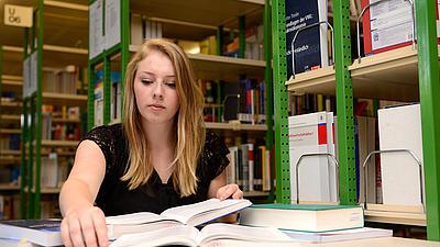 Eine Studierende sitzt in einer Bibliothek.