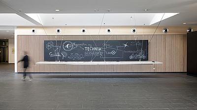 In einem hellen Foyer mit Säule und dunklen Bodenfliesen hängt unter einem großen Lichtschacht ein langes flaches Objekt, an dem eine Person vorbeigeht.