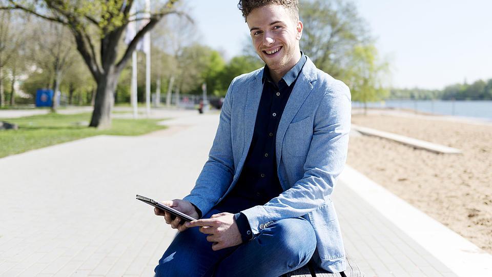 Ein junger Mann sitzt lächelnd auf einer Parkbank im Sonnenschein. In seiner Hand hält er ein Tablet.