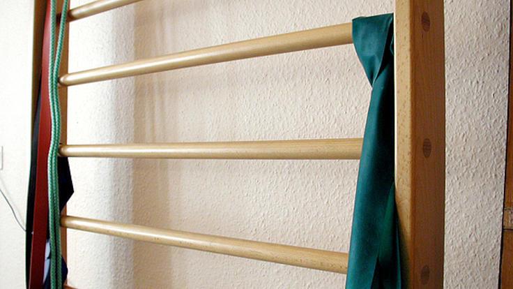 Vor einer weißen Wand steht eine Sprossenwand aus Holz an der verschiedenfarbige Tücher angebunden sind.