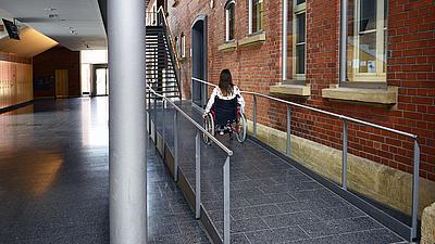 Eine Rollstuhlfahrerin fährt eine Rampe hoch.