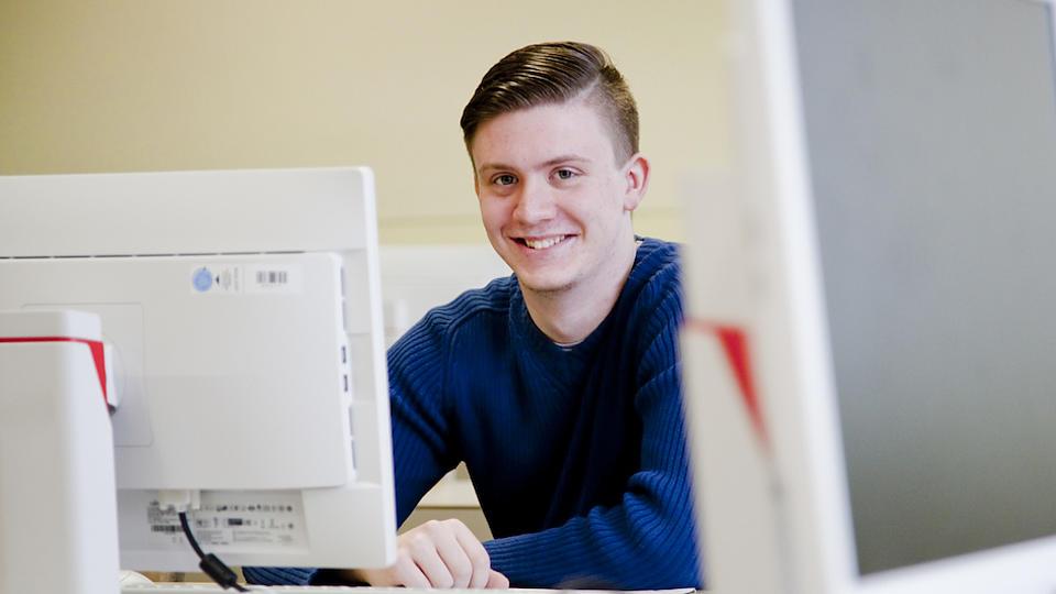 Ein junger Mann sitzt an einem Computerbildschirm.