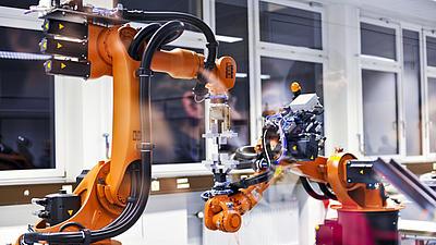 Zwei orangefarbene Industrieroboter, die sich in einer Werkhalle befinden, arbeiten gemeinsam an einem Experiment.