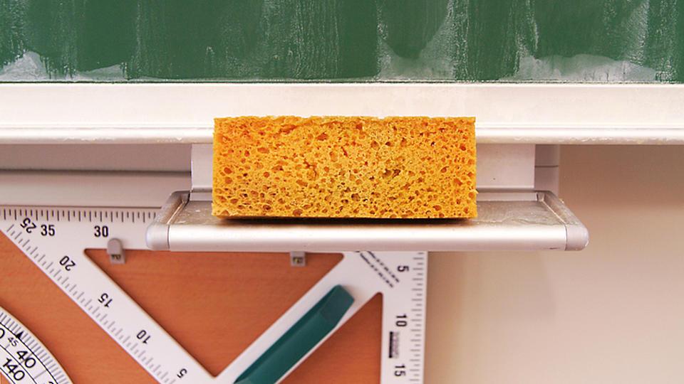 Detailaufnahme der Ablage für einen Schwamm an einer großen grünen Schulwandtafel, auf der ein großer quadratischer Schwamm abgelegt wurde. Unter der Tafel hängen große Zeichenwerkzeuge für die Tafel.