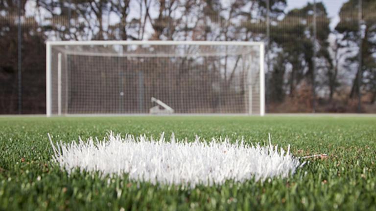 Fußballrasen mit einer Ballmarkierung und einem Fußballtor, aufgenommen vom Abstoßpunkt sehr weit unten über dem Rasen.