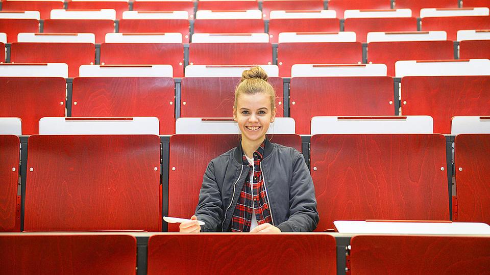 Eine junge Frau sitzt lächelnd in der zweiten Reihe einer roten Hörsaalbank.