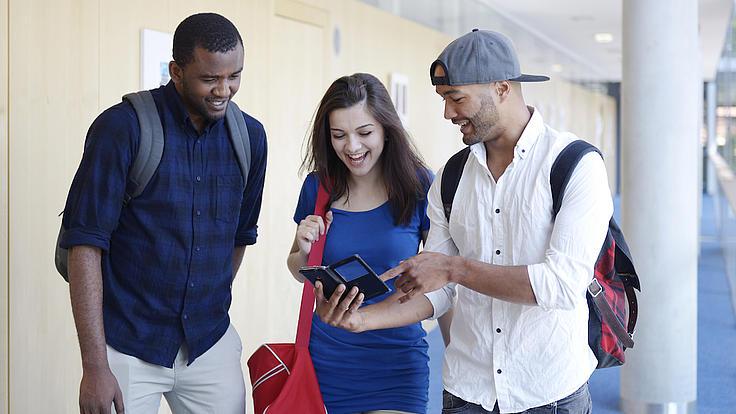 Eine junge Frau und zwei junge Männer stehen in einem Flur zusammen und schauen gemeinsam auf ein Smartphone,