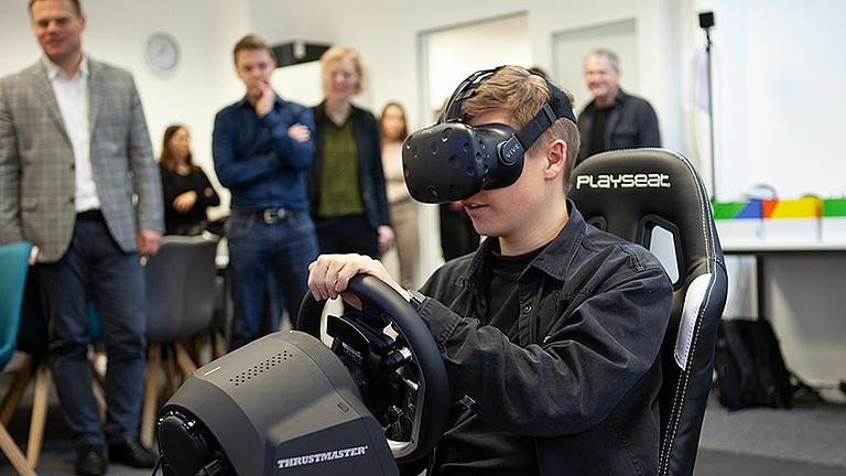 Studierender sitzt mit einer VR-Brille auf dem Kopf in einem Playseat mit Lenkrad.
