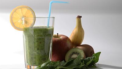 Auf einer hellen Oberfläche steht ein Glas mit einem grünen Smoothie.