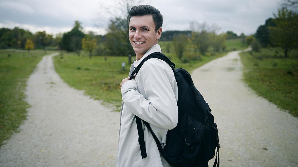 Ein junger Mann steht an einer Weggabelung.