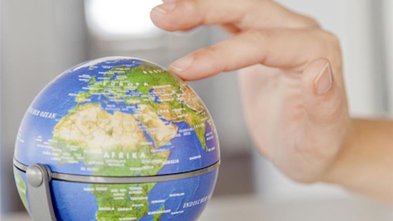 Auf einem kleinen Weltglobus wird mit dem Zeigefinger einer Hand ein Land angedeutet.