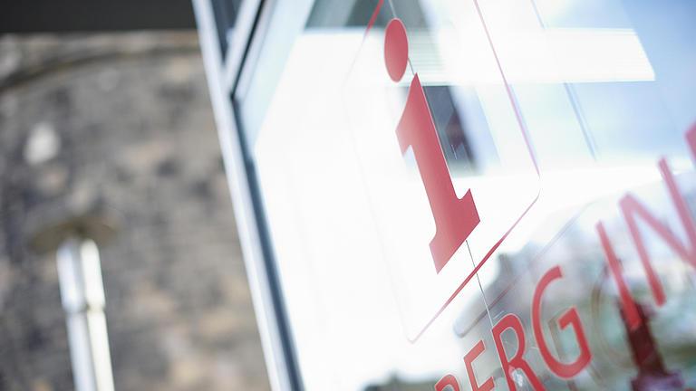 EIn rotes i für Information steht auf einer Glasscheibe.