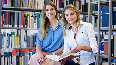 Studierende suchen in der Bibliothek nach passenden Büchern