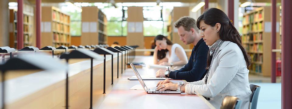 Studierende sitzen und lernen in einer Bibliothek.