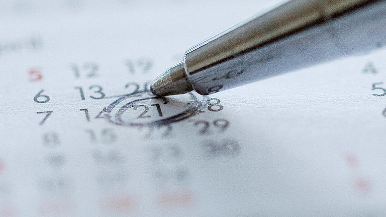 Ein silberfarbener Kugelschreiber kreist mit seiner Minenspitze die Zahl 21 auf einem Kalender ein.