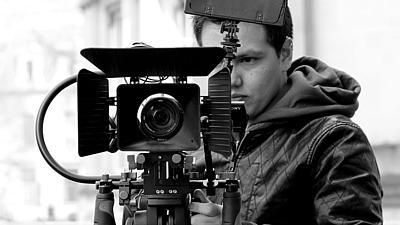 Foto von Camilo Berstecher hinter einer Filmkamera.