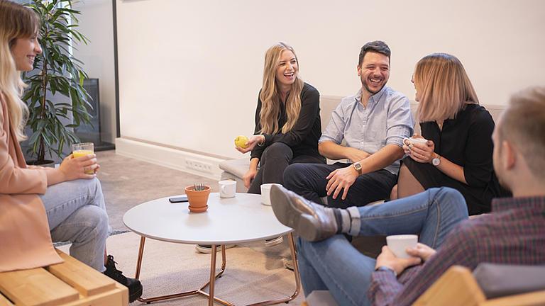 Eine Gruppe Studenten sitzend auf einer Couch unterhalten sich