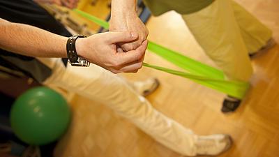 Auf hellem Holzboden sieht man zwei männliche Personen brustabwärts. Die eine Person wird von der anderen bei einer Übung mit einem leuchtend grünen Fitnessband angeleitet.