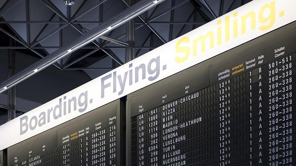 Von unten aufgenommenes Foto der Ankunfts- und Abflugtafeln eines internationalen Flughafens.