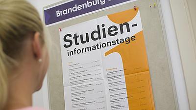 Eine junge Frau schaut sich ein Plakat zu einem Studieninformationstag an.