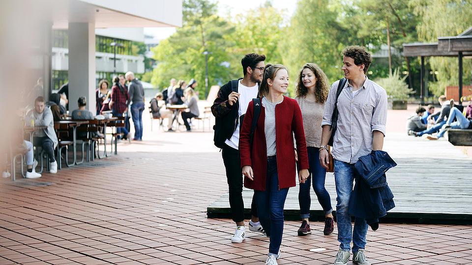 Zwei junge Frauen und zwei junge Männer laufen auf einem breiten Weg vor der Universität..
