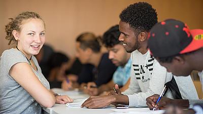 Mehrere Studierende sitzen an einem Tisch.