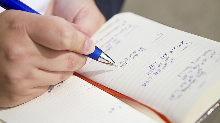 Nahaufnahme eines Notizbuches, das von einer Hand gehalten wird. In der andren Hand wird eine blauer Kugelschreiber gehalten.