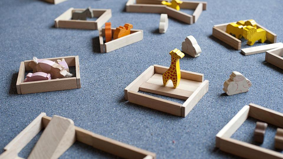 Auf einem grauen Fußboden sind verschiedene Holzspielzeugtiere und andere Holzspielzeuge aufgebaut
