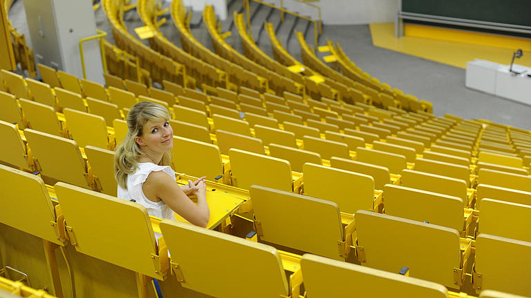Eine junge Frau sitzt in einem Vorlesungssaal mit gelben Stühlen.
