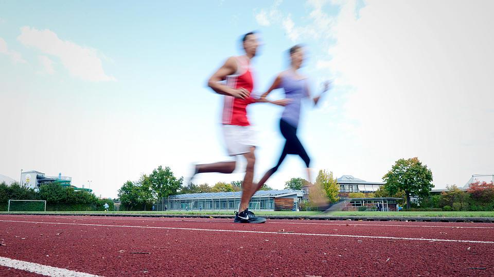 Ein Mann und eine Frau joggen über einen Sportplatz.