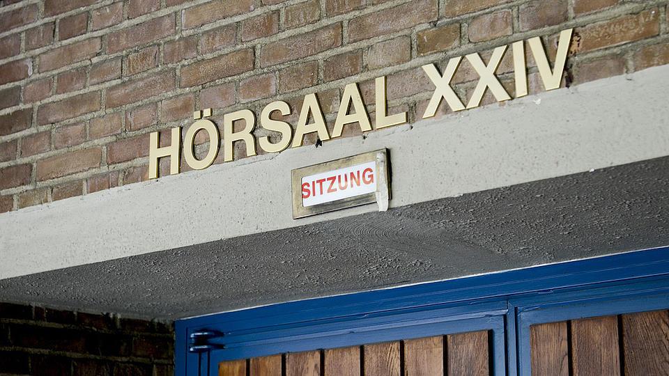 Nahaufnahme einer Raumbezeichnung in einem Hochschulgebäude. Über einer Holztür mit blauem Rahmen steht in Großbuchstaben