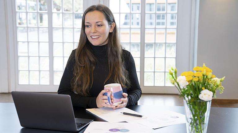 Eine Frau vor Ihrem Laptop mit einer Kaffeetasse in der Hand