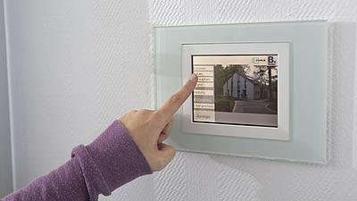 Die Hand einer Frau bedient ein Touchpad einer smarten Steuerungseinheit für ein Einfamilienhaus.