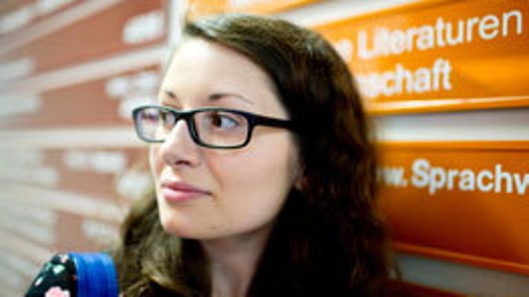 Eine Studentin steht vor Wegweisern in einer Uni.