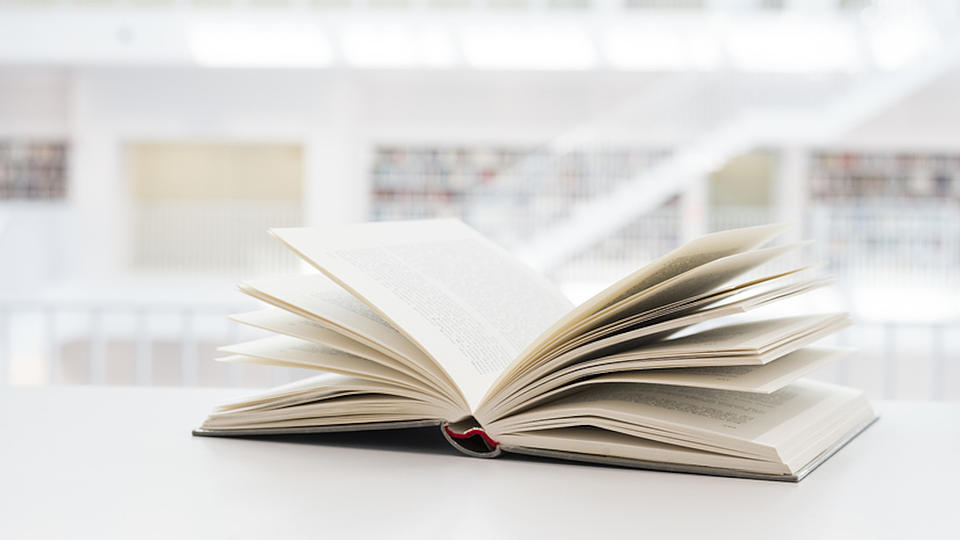 Auf einer hellen Oberfläche liegt ein aufgeschlagenes Buch.