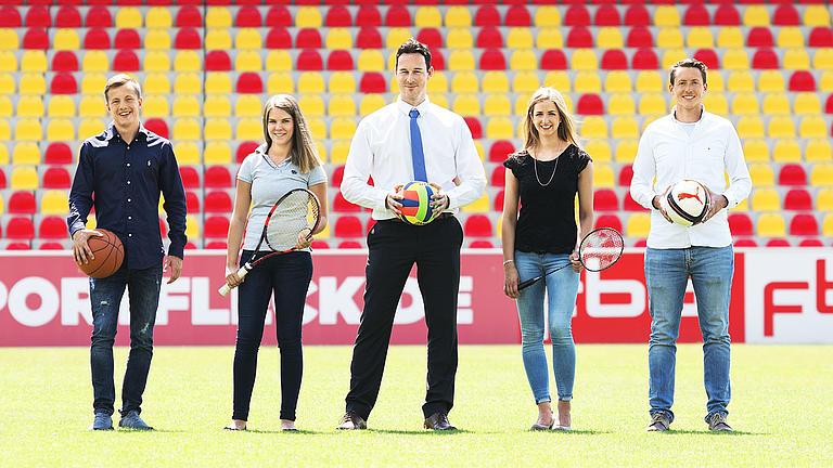 Fünf Studierende stehen mit Sportgeräten auf einem Sportplatz.
