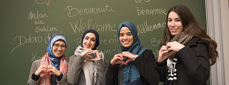 Vier Studierende zeigen Herzen mit ihren Händen.