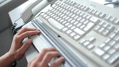Ein Mann arbeitet mit einer Braille-Tastatur.