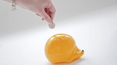 Eine Frau wirft zwei Euro in ein gelbes Sparschwein in Igelform.